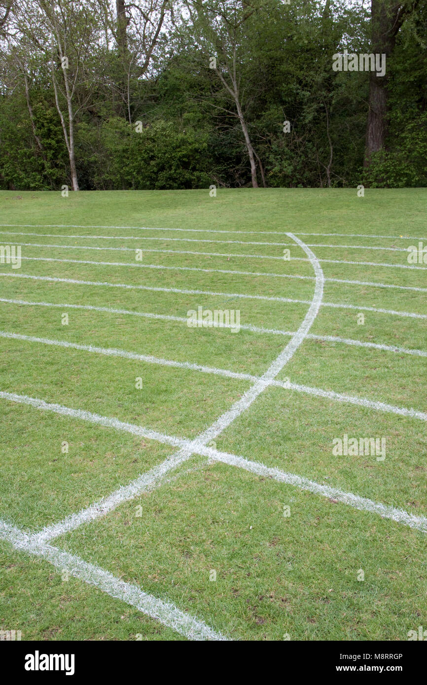 Curved white line on a grass running track - Stock Image