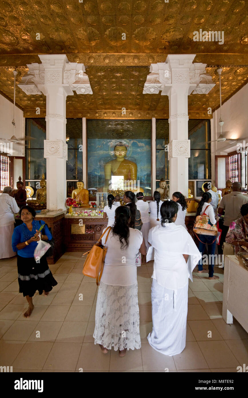 Local people and pilgrims praying and giving flower gifts at the Jaya Sri Maha Bodhi temple in Anuradhapura, Sri - Stock Image
