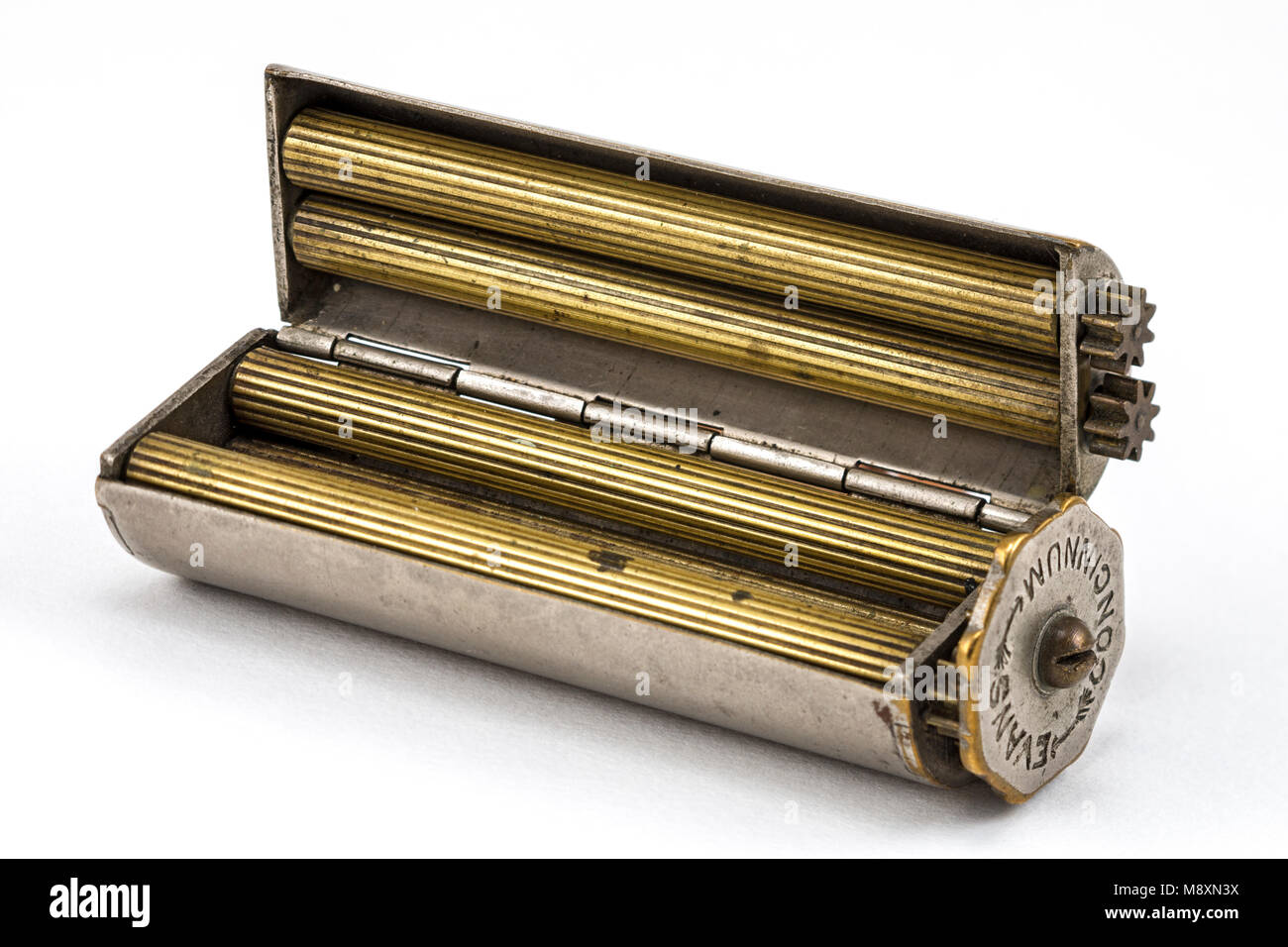 An Evans Patent Concinnum Machine, a vintage cigarette rolling device.  Internal view, showing the brass rollers. Stock Photo