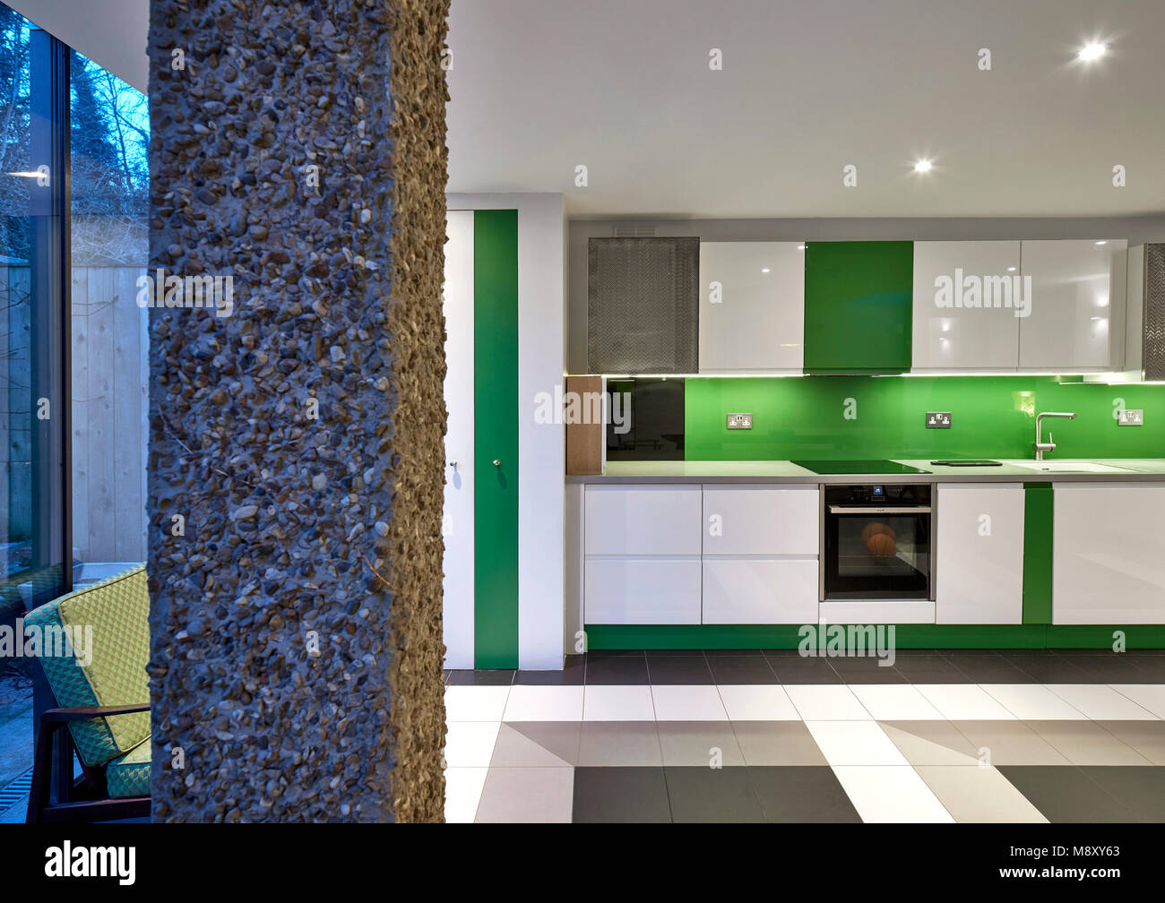 Side view towards kitchenette at dusk. Sean Griffiths, London, United Kingdom. Architect: Sean Griffiths , 2018. - Stock Image