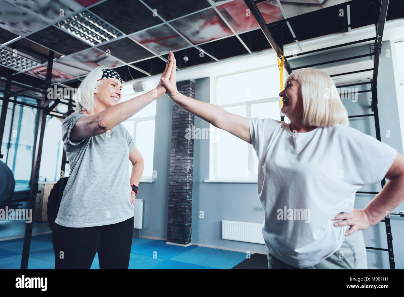 Senior female friends high fiving at gym - Stock Image