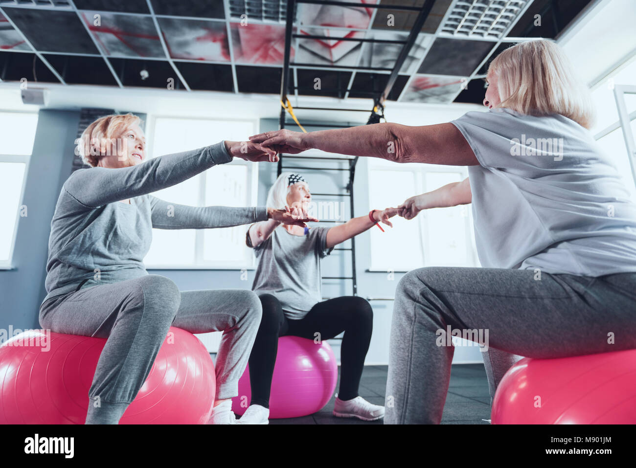 Smiling senior ladies joining arms while sitting on fitness balls - Stock Image