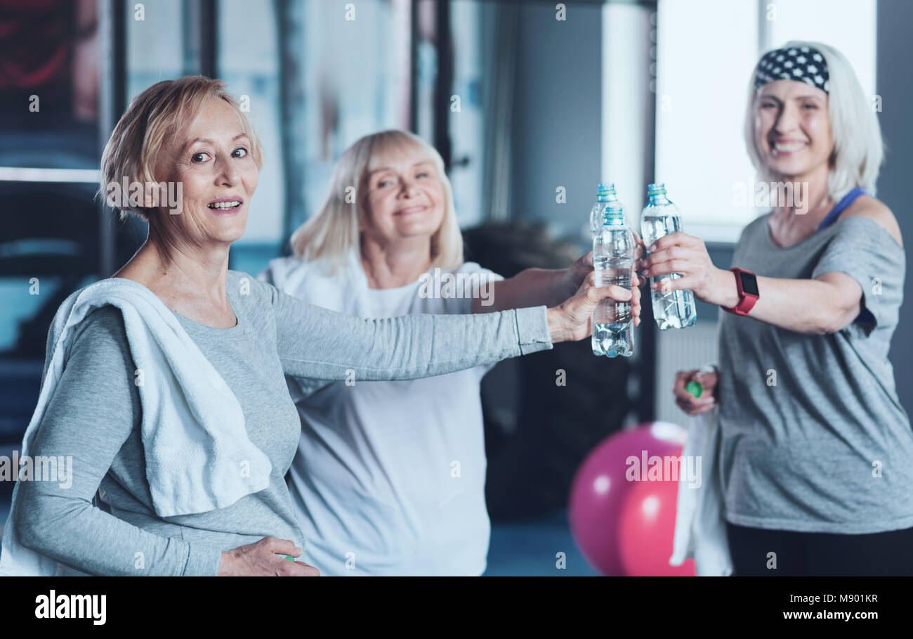 Positive minded retired friends joining bottle of water after training - Stock Image
