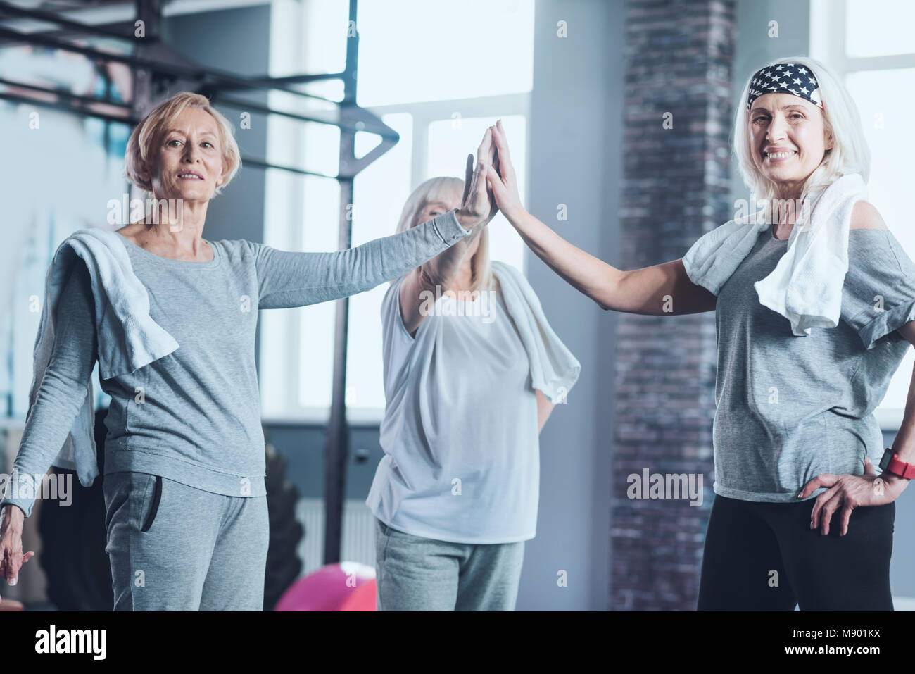 Mature women joining hands together at gym - Stock Image
