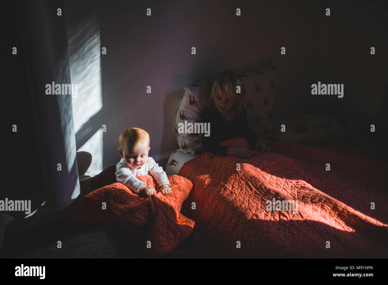 baby in babydoll cradle dramatic light trendy kids room - Stock Image