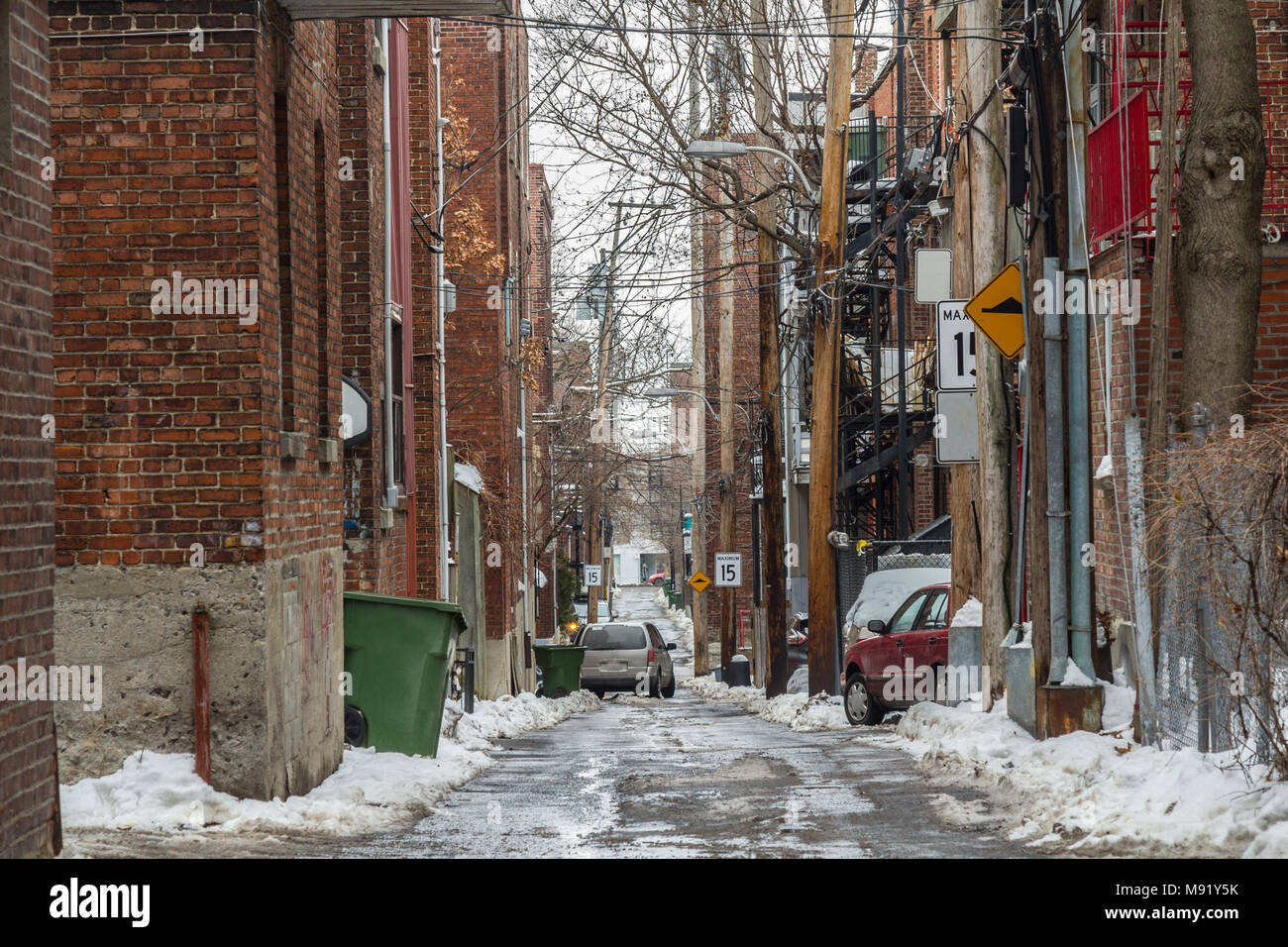 Typical North American residential dead-end alley street covered in snow in a residential part of Montreal, Quebec, Canada  Picture of a dilapidated a - Stock Image