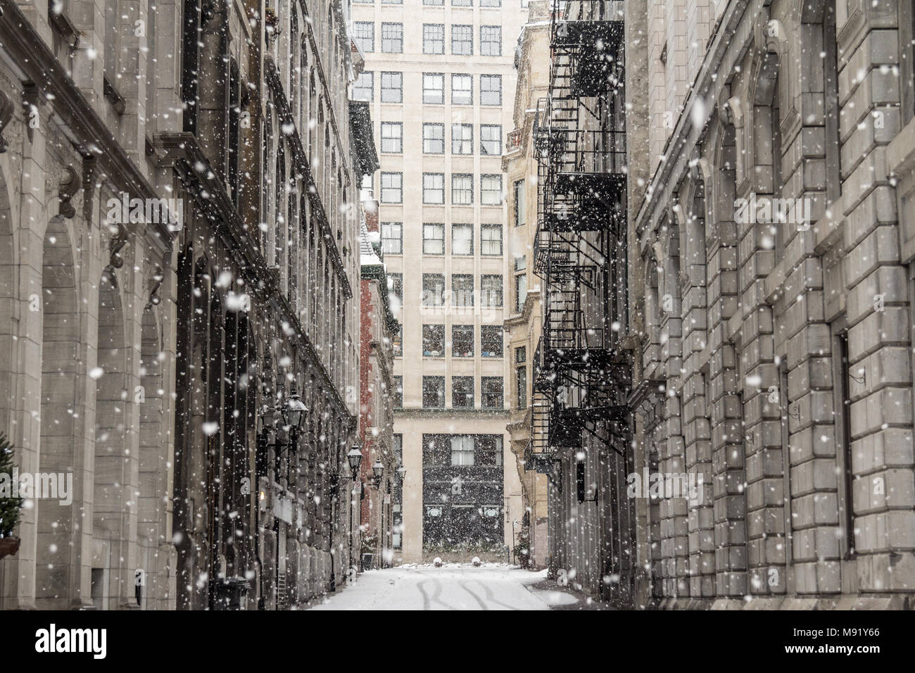 Street Alley of Old-Montreal in winter under a snow storm with a modern skyscraper in the background  Picture of a small alley street in the older par - Stock Image
