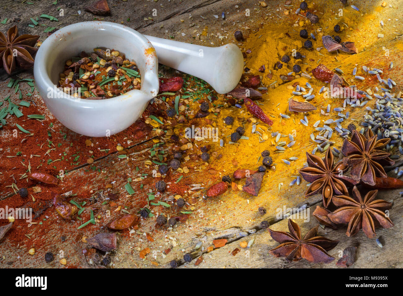 Crushing herbs and spices in a mortar and pestle in a rustic farmhouse kitchen. - Stock Image