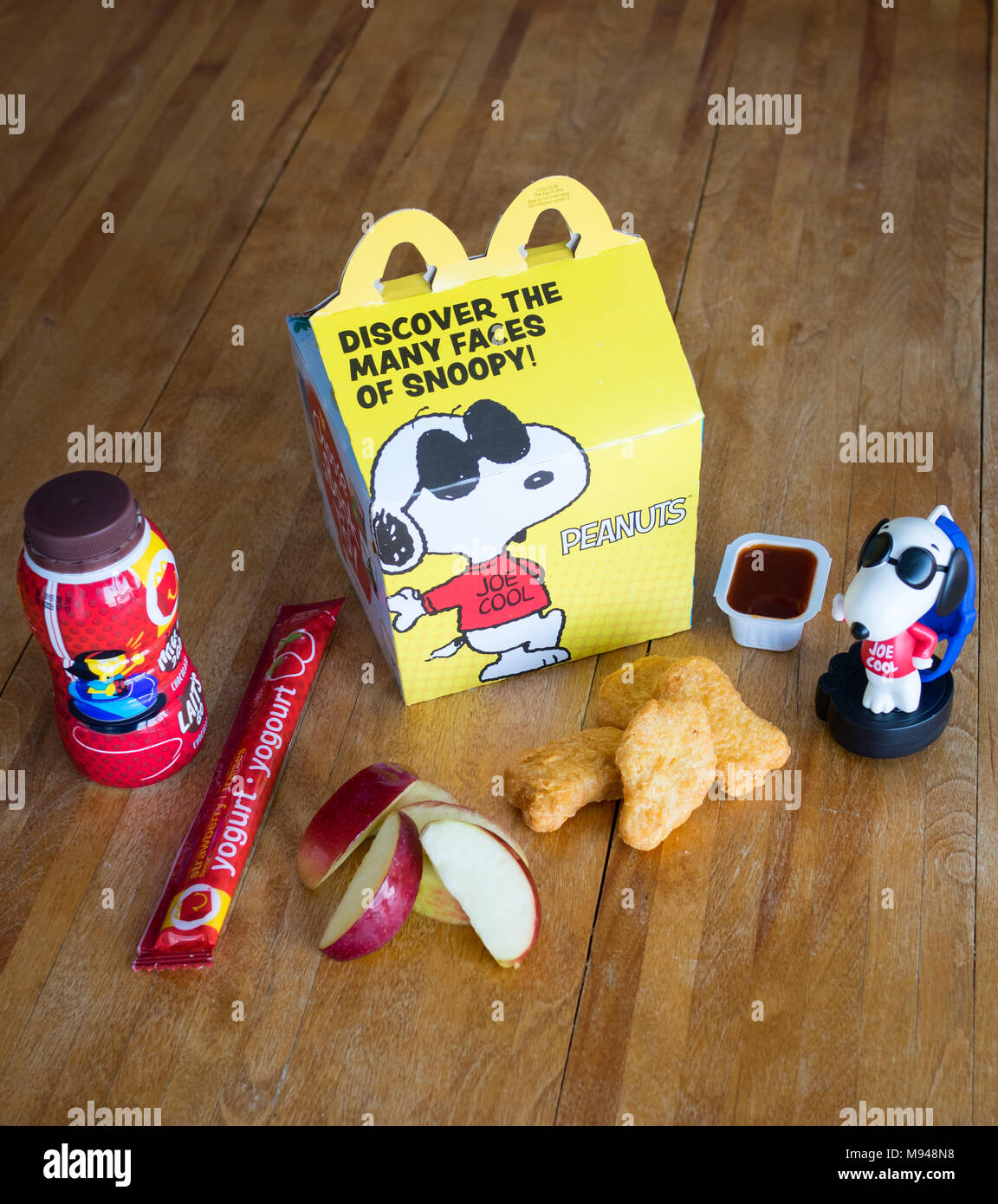 A McDonald's Happy Meal with Chicken McNuggets, apple wedges, chocolate milk, yogurt tube, and Snoopy toy. - Stock Image
