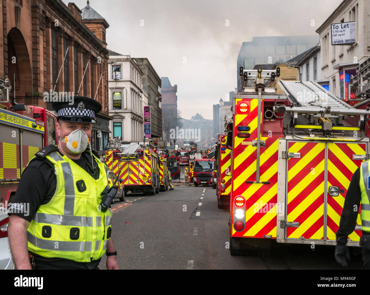 Hope Street, Glasgow, Scotlnad, United Kingdom, 22nd March 2018. A major fire involving multiple buildings closes streets in central Glasgow. Fire engines attend the incident. A policeman wears a mask due to the risk of asbestos from the smoke Stock Photo
