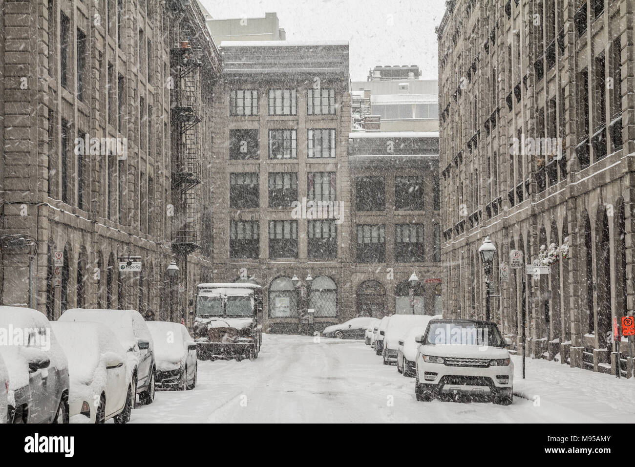 MONTREAL, CANADA - DECEMBER 29, 2016: Street Alley of Old-Montreal in winter under a snow storm with a modern skyscraper in the background  Picture of - Stock Image
