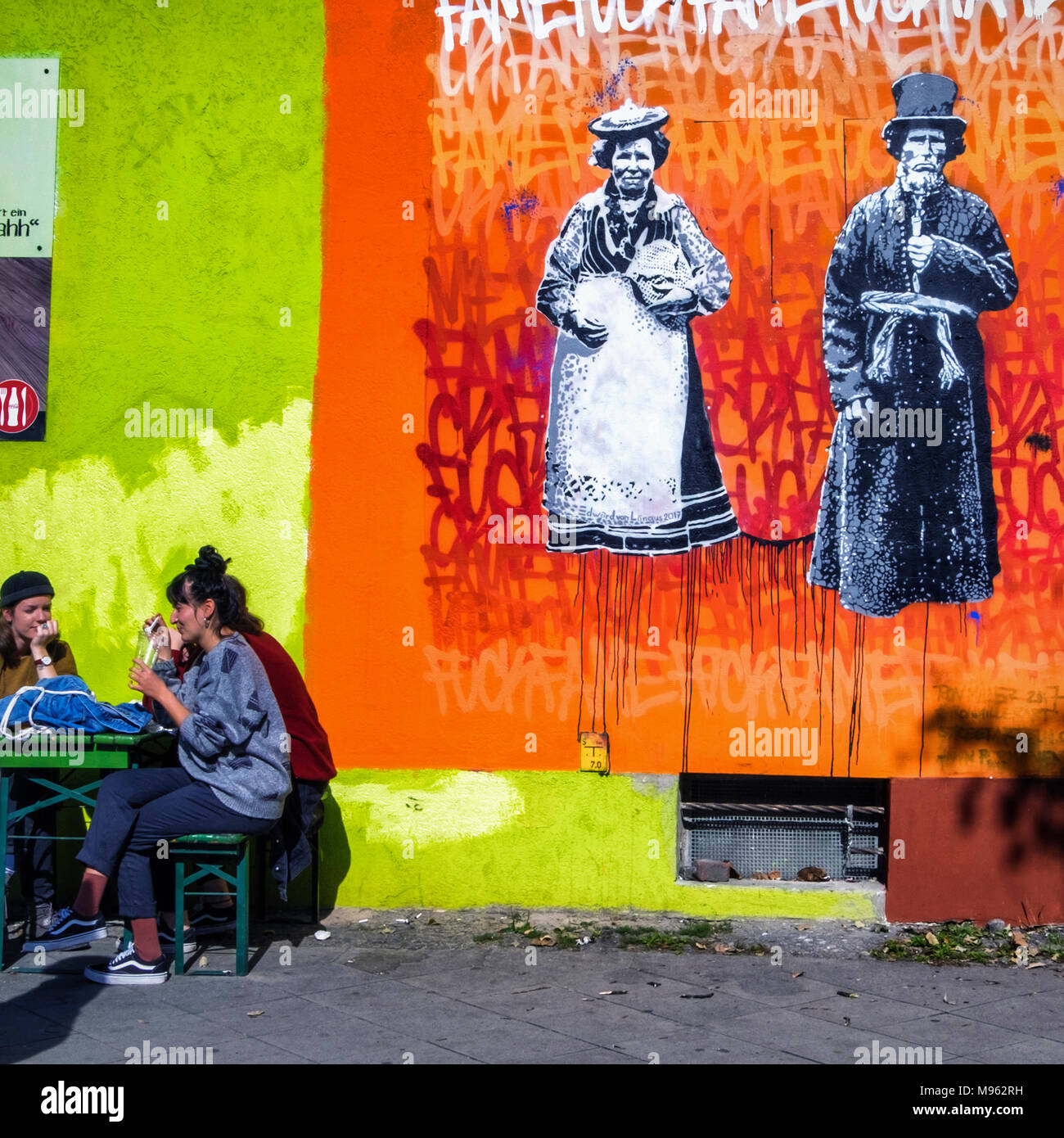 Berlin Mitte, Two young women sit in the sun next to colourful street art work By Estonian street artist, Edward von Lõngus - Stock Image