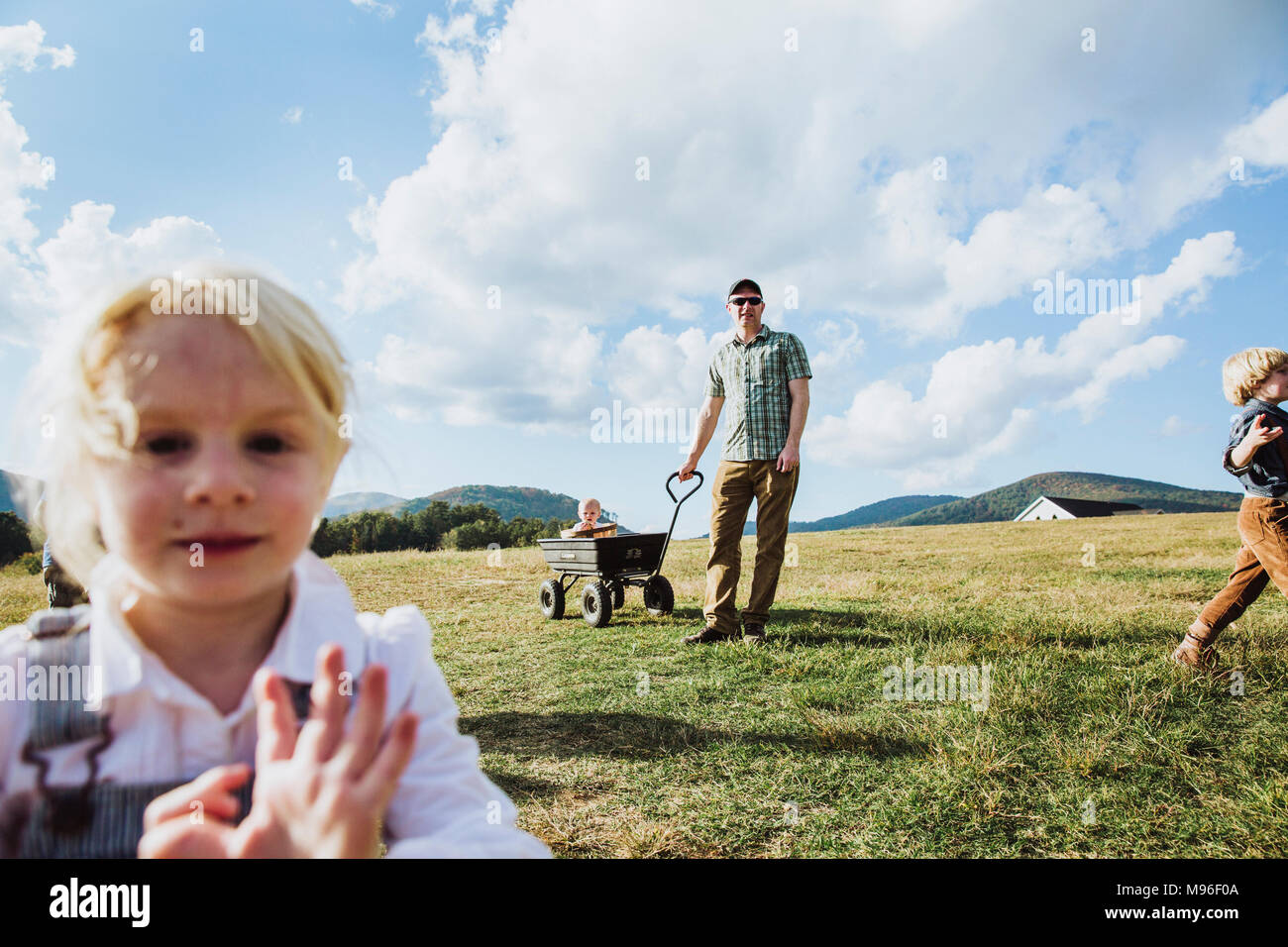 Family with wagon in apple farm - Stock Image