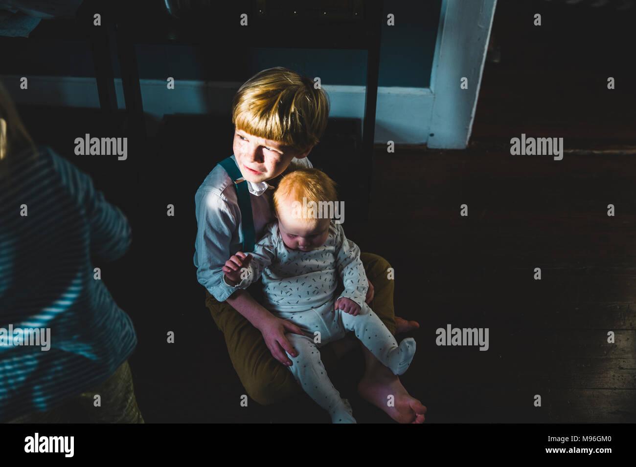 Baby sitting on boy's lap - Stock Image