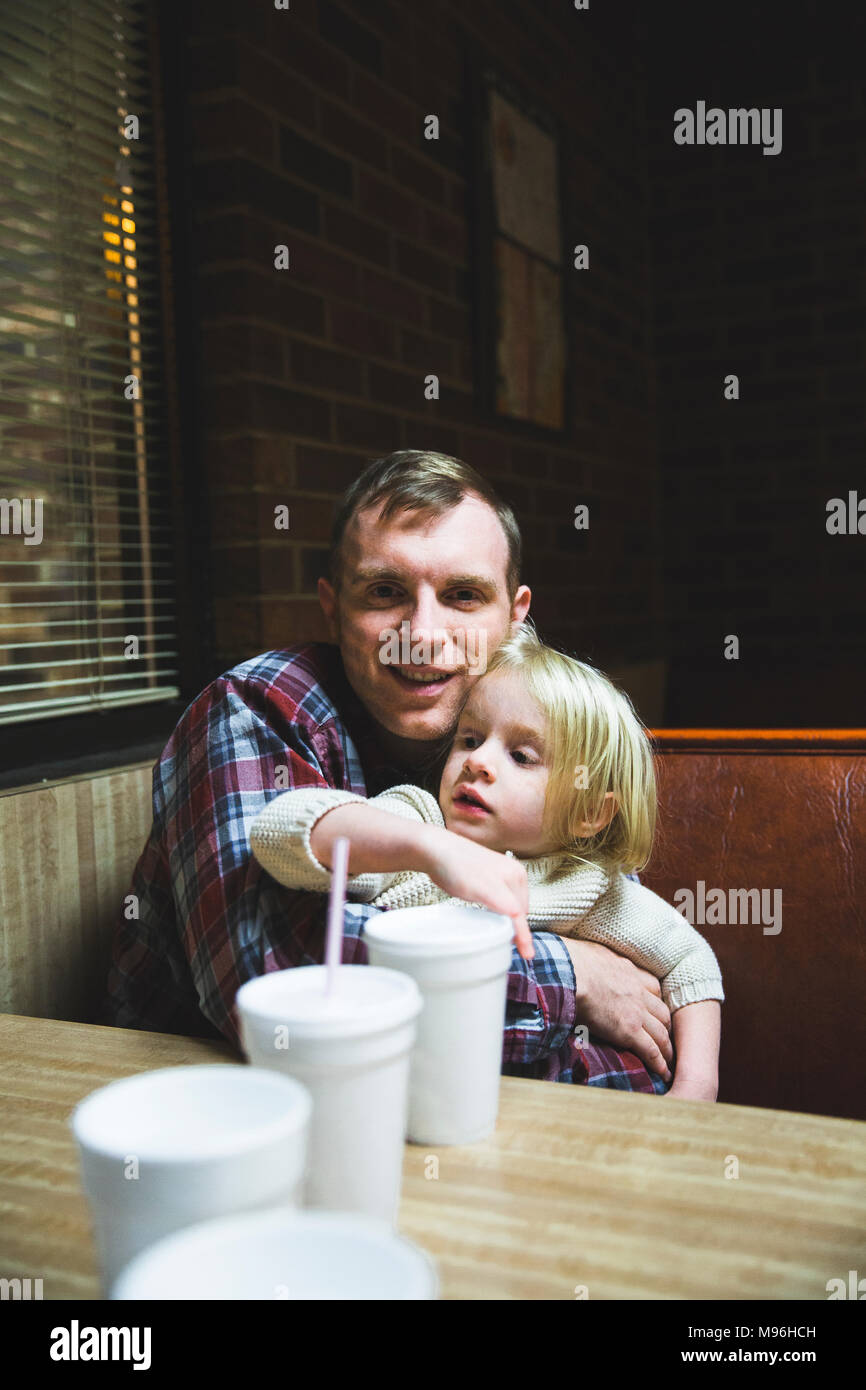 Man holding daughter in diner booth with plastic cups on table - Stock Image