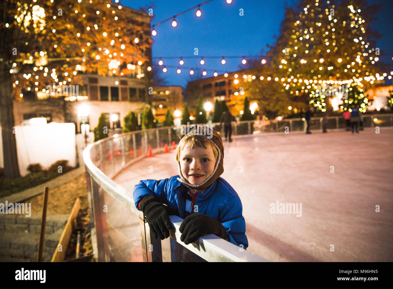 Boy looking at camera at the side of a skating rink - Stock Image