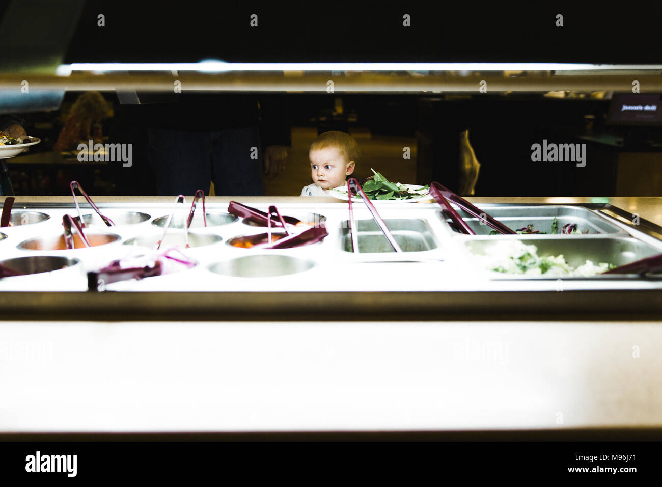 Baby looking over salad bar - Stock Image