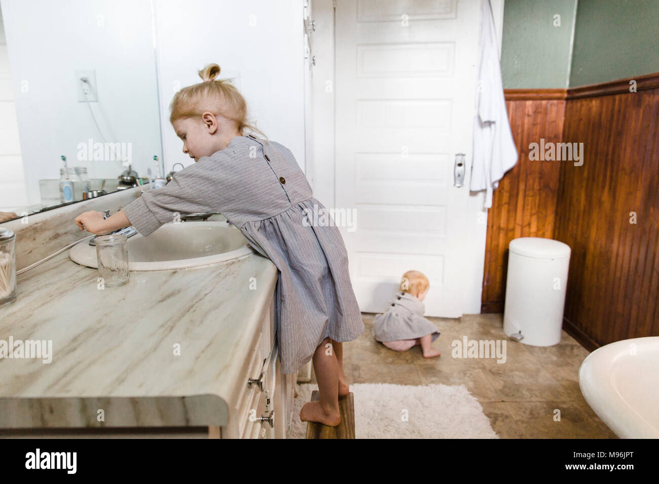 Girl using sink whilst baby sits on bathroom floor - Stock Image