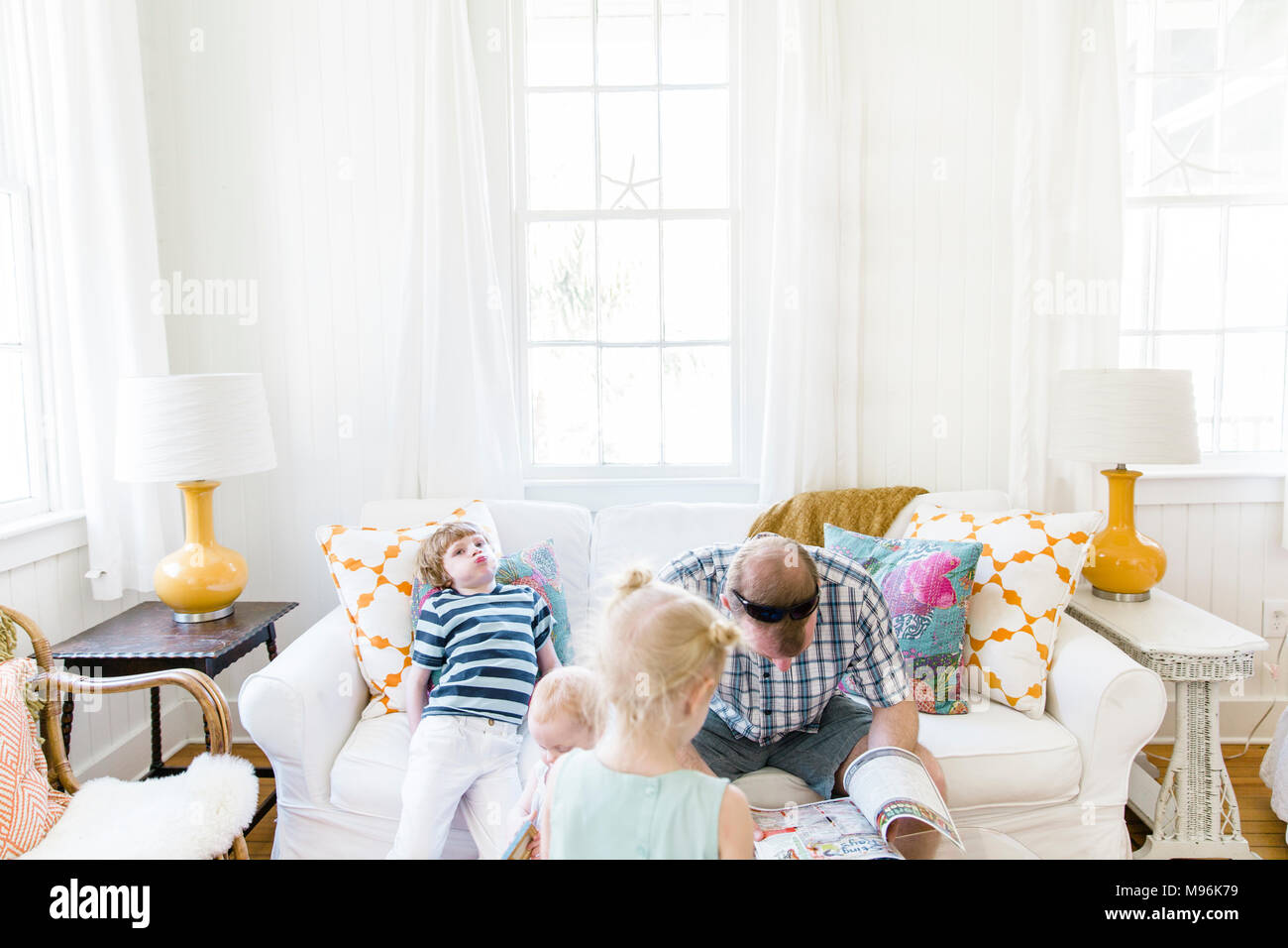 Man reading on sofa with children around him - Stock Image
