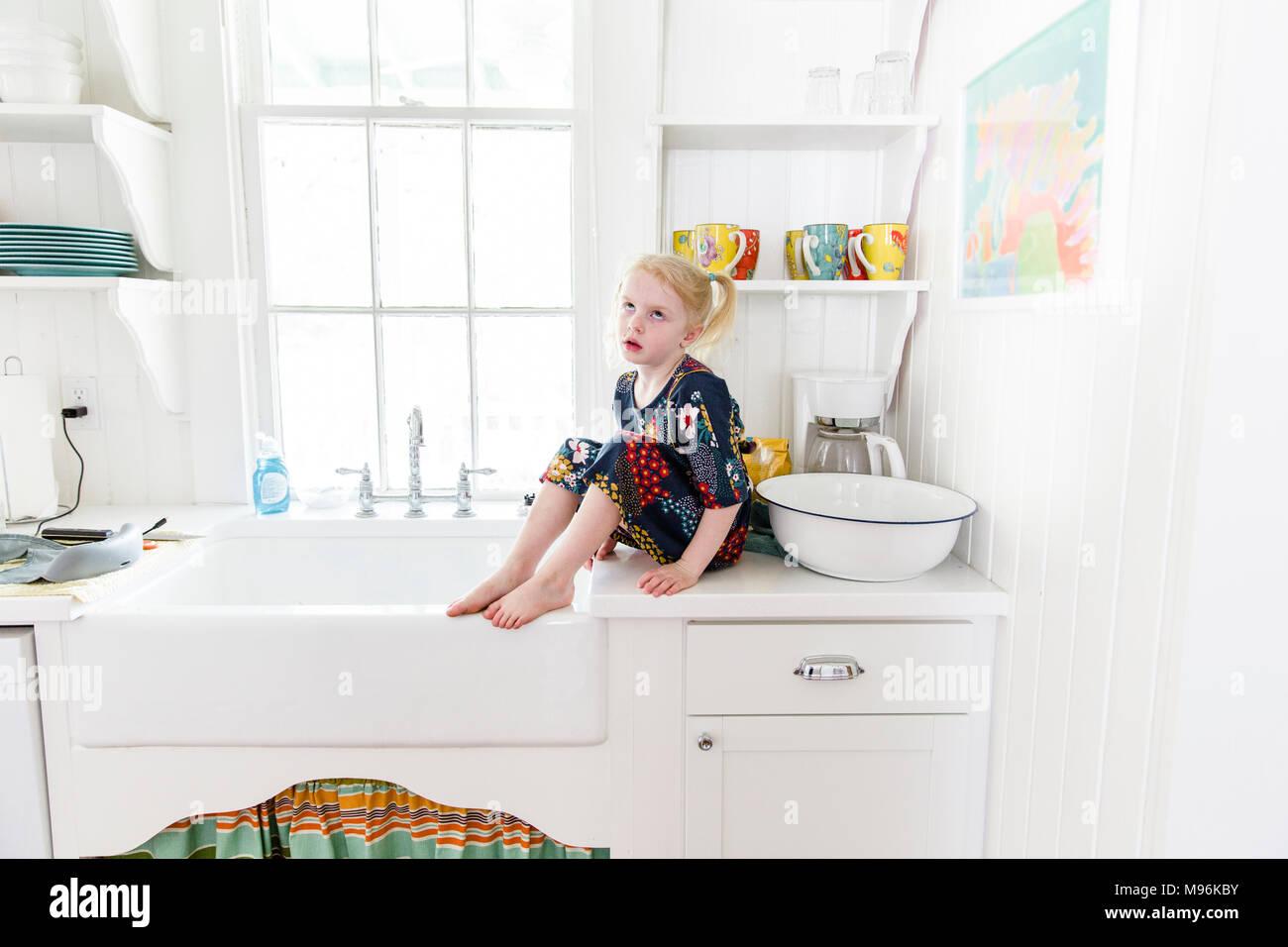 Girl rolling eyes sitting on kitchen worktop - Stock Image
