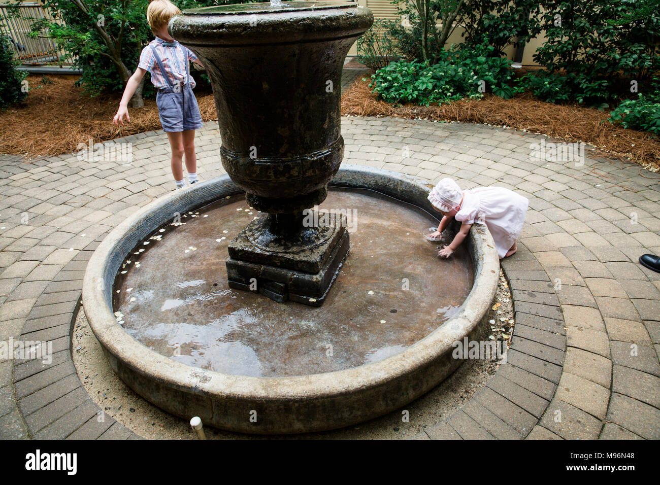 Baby and other children playing around fountain - Stock Image