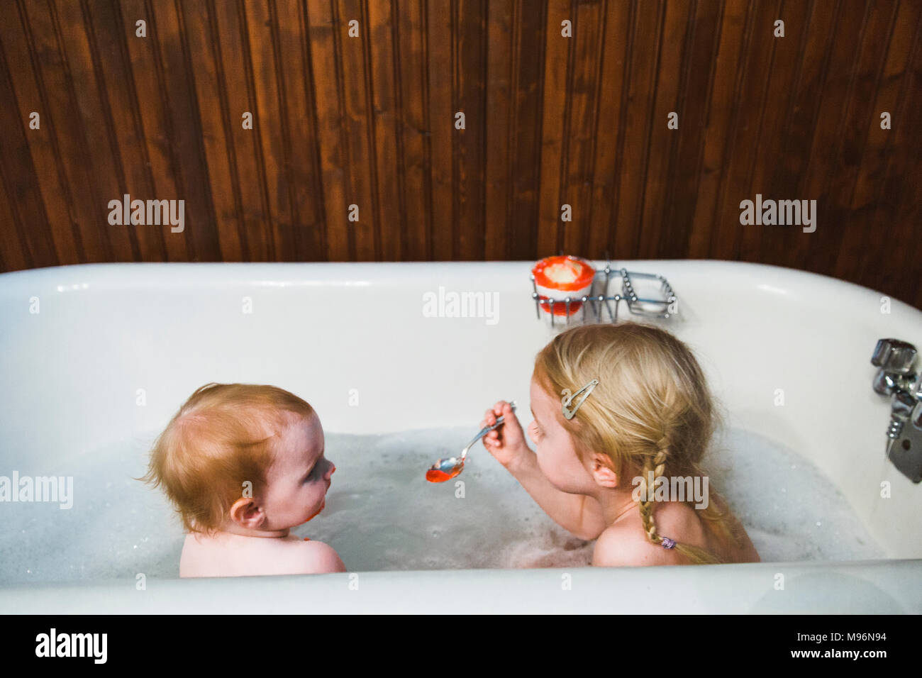 Child getting fed in the bath by another child - Stock Image