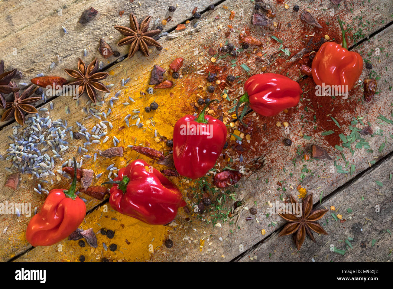 Hot chili peppers on a rustic farmhouse table. Used to add a hot spicy flavor to cooking. - Stock Image