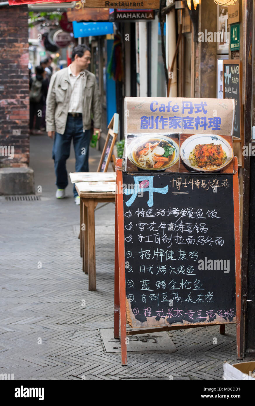 Man walking past a cafe in Shanghai, China - Stock Image