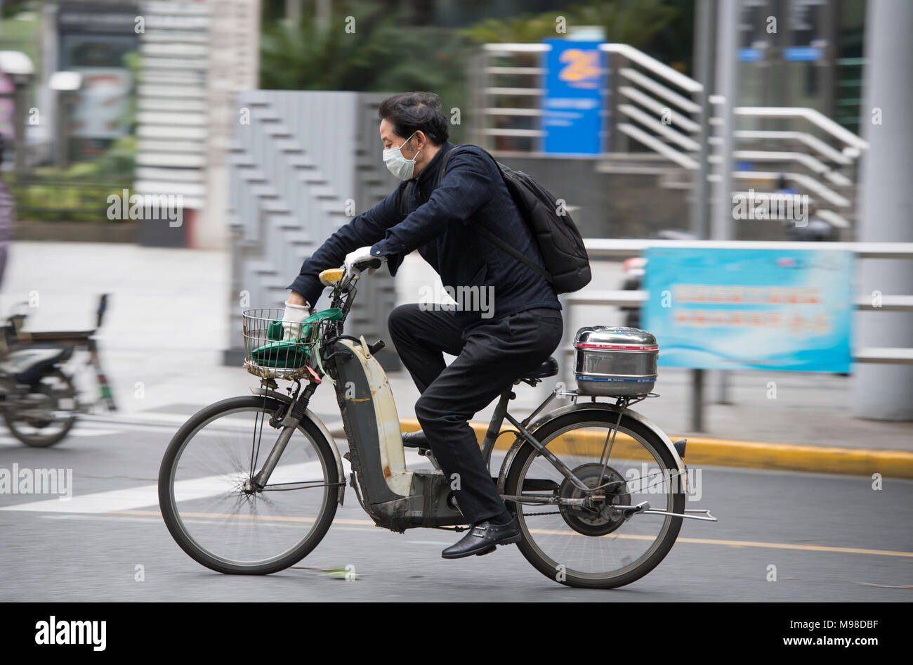 Man wearing a face mask riding a scooter in Shanghai, China - Stock Image