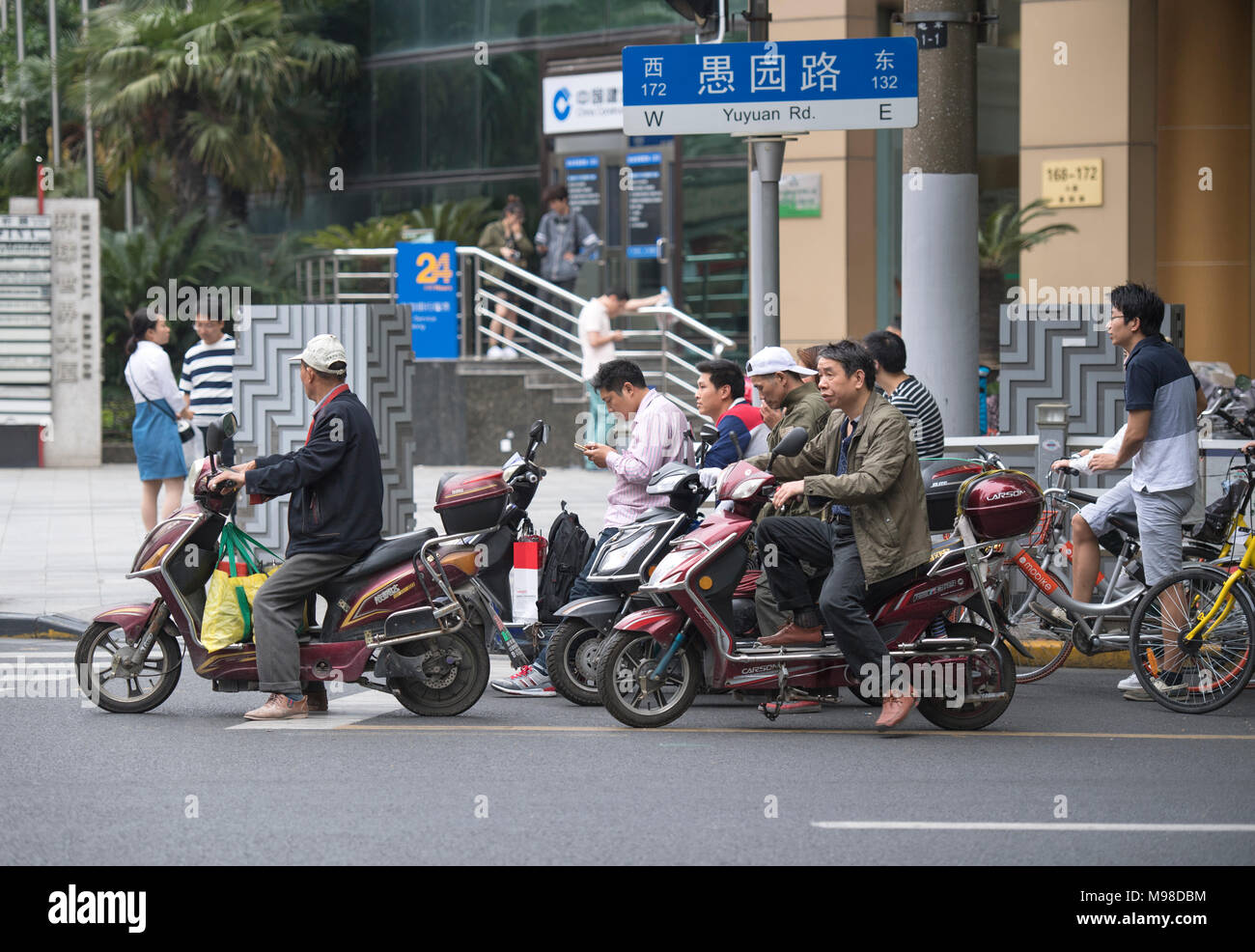 People riding bikes and scooters on the streets on Shanghai in China - Stock Image