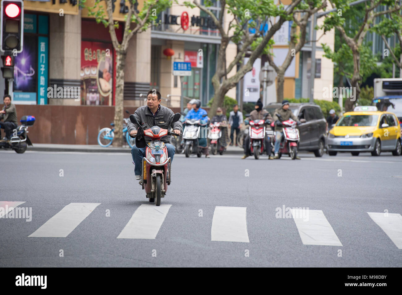 Man riding a scooter through the streets of Shanghai in China - Stock Image