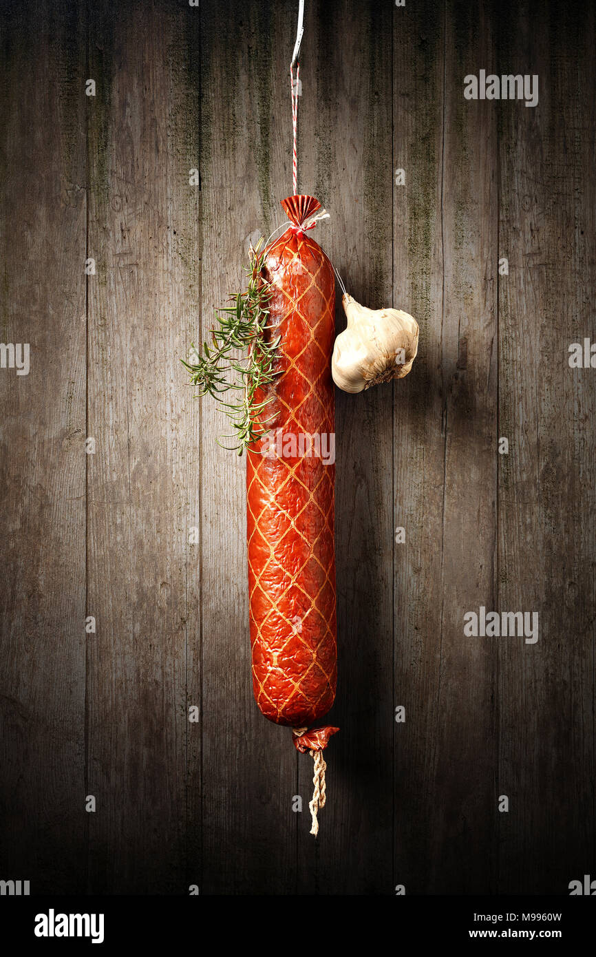 Salami Sausage hanged to dry with Garlic and Rosemary against an old rustic wooden wall - Stock Image