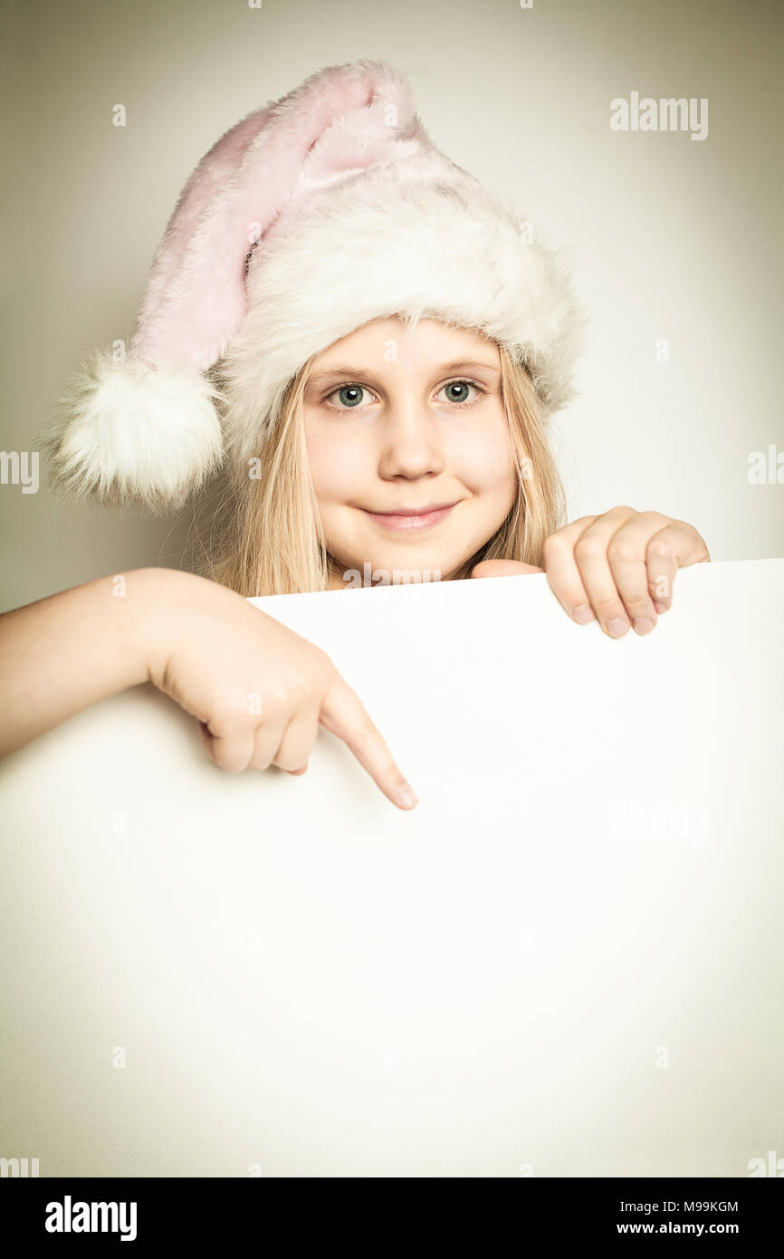 6667fa51c30 Child girl dressed in Santa Claus hat with paper blank. Christmas concept