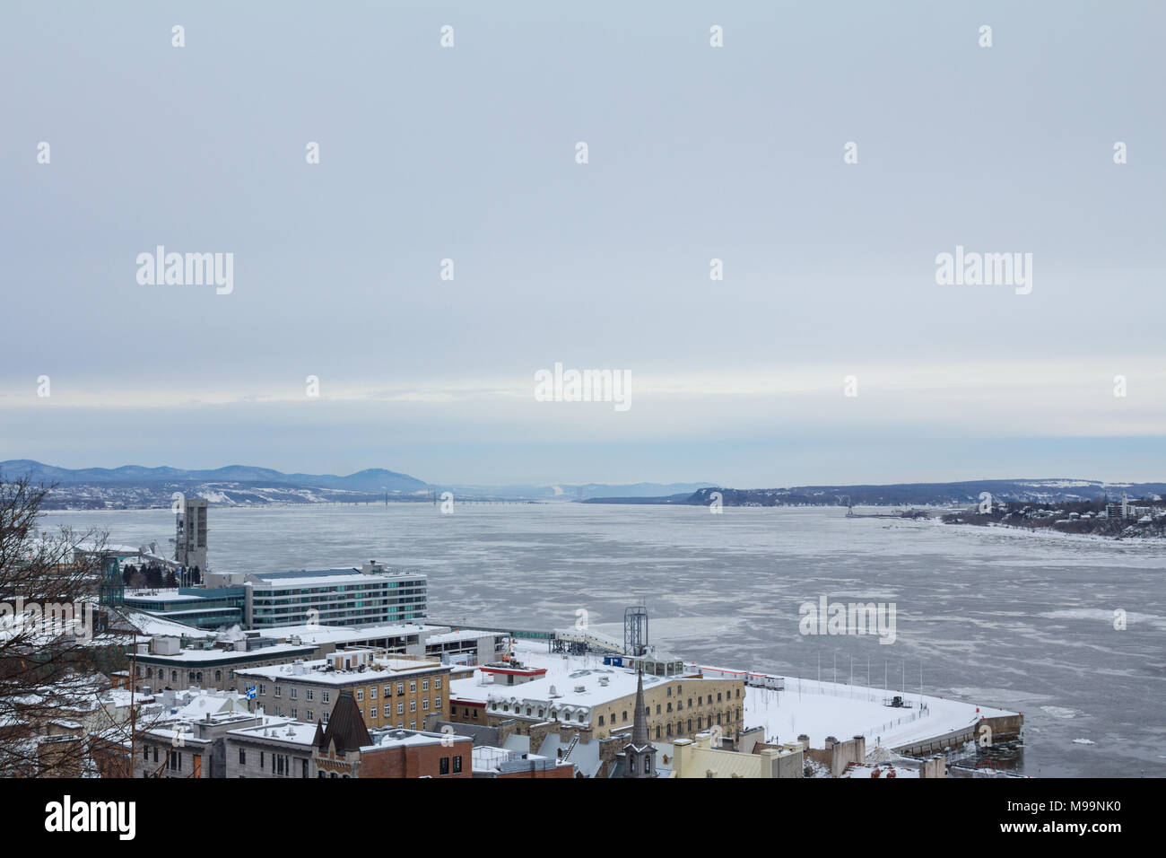 Panorama of frozen Saint Lawrence river (fleuve Saint Laurent) in Quebec city during a winter afternoon. Saint Lawrence is one of the main rivers of C - Stock Image