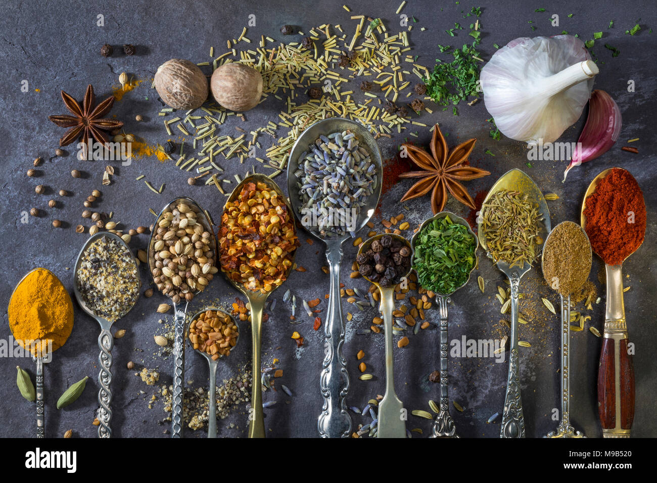 Spices on spoons - a selection of spices used to add flavor to cooking. - Stock Image
