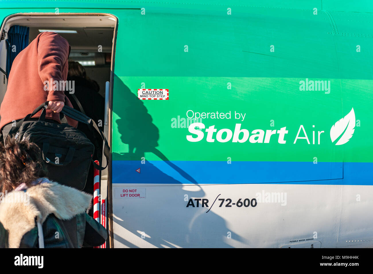 Passengers board an Aer Lingus/Stobart Air ATR 72-600 aircraft at Birmingham Airport heading to Cork, Ireland with copy space. Stock Photo