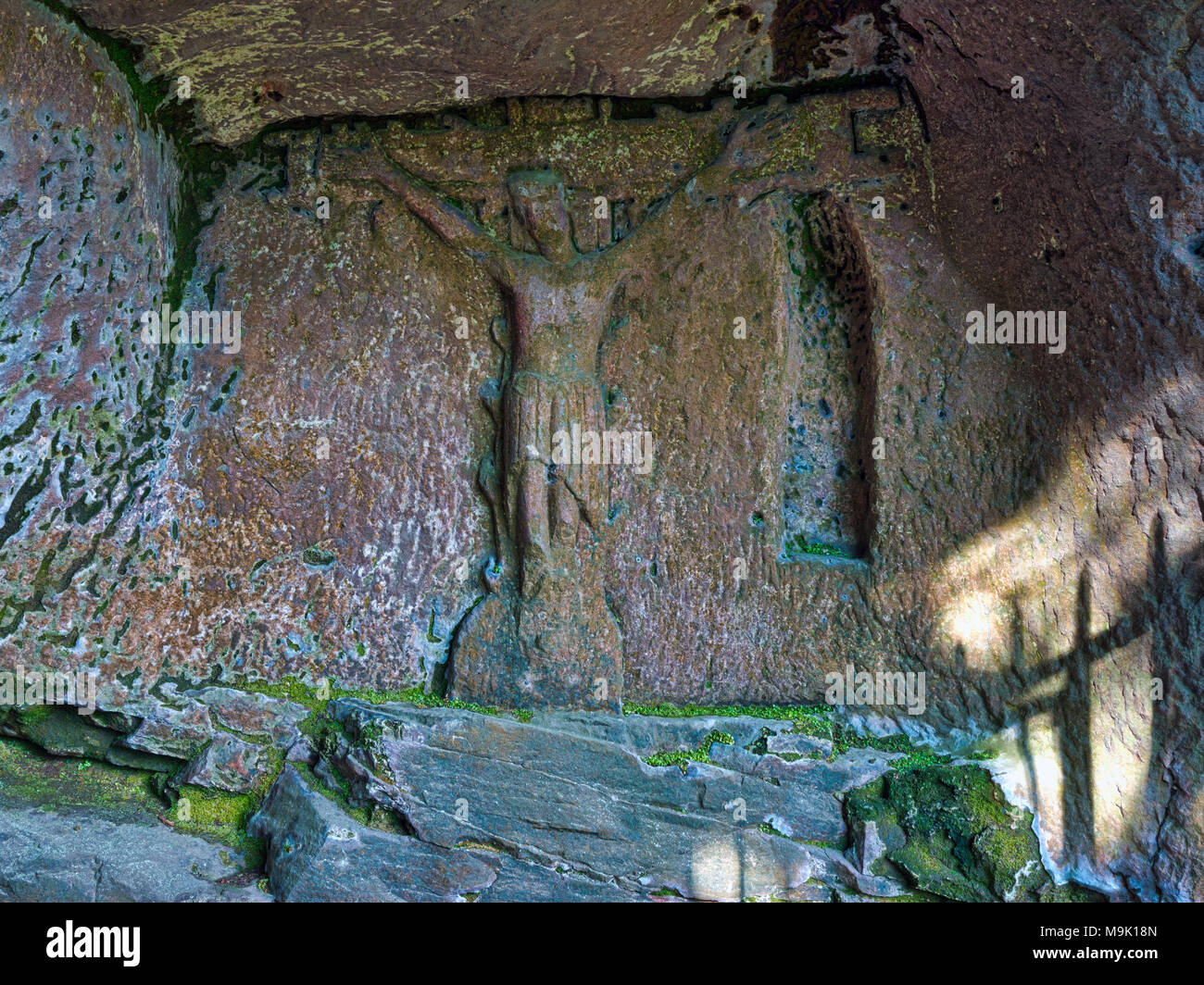 14th century Hermit's Cave at the base of Cratcliffe Rocks, near the village of Elton, Derbyshire, within a four feet high stone carved Jesus Christ - Stock Image