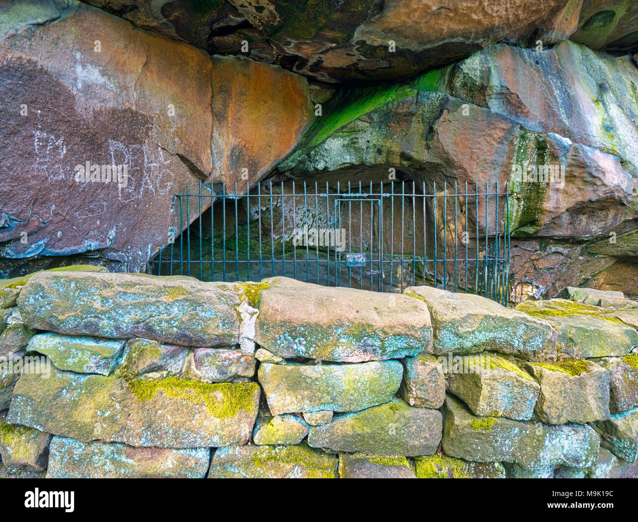 New graffiti scratched into the rocks on the 14th century Hermit's Cave at the base of Cratcliffe Rocks, near the village of Elton, Derbyshire - Stock Image