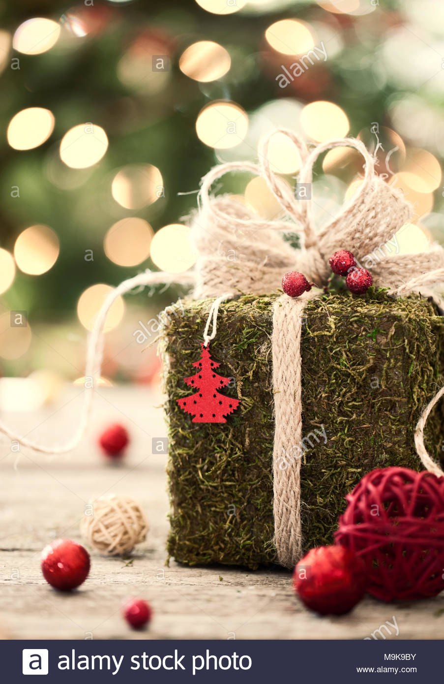 Eco environmentally friendly, holiday christmas moss gift on rustic wood - Stock Image