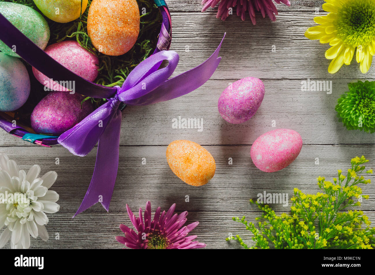 Easter Basket with Eggs and Flowers on White Rustic Table - Stock Image