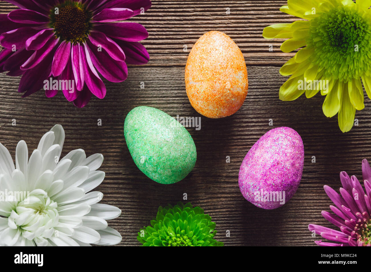 Colorful Eggs and Flowers on Wood Table - Stock Image