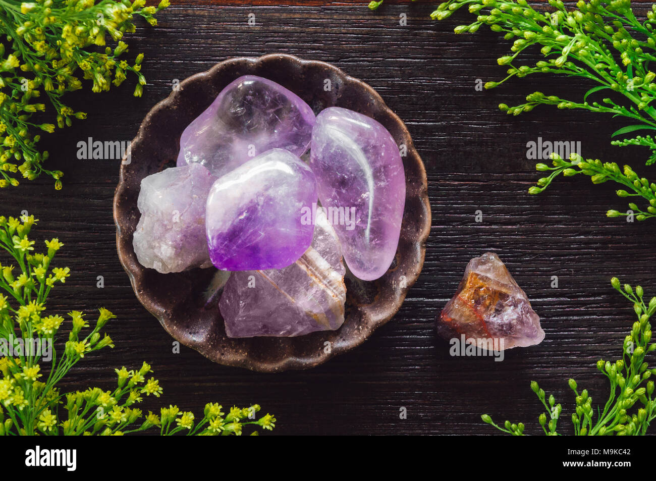 Ceramic Bowl of Amethyst Crystals with Yellow Aster Solidago Flowers - Stock Image