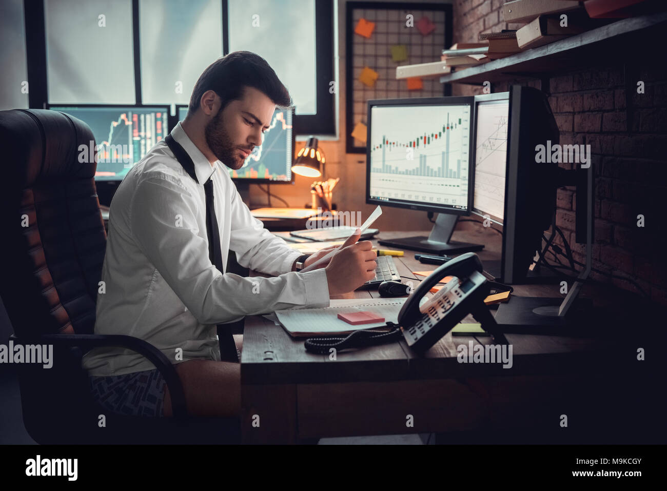 Trader analyzing financial trading charts and computer screen for  successful sell buy strategy of stock market investment. Indoor, studio  shot. Work,