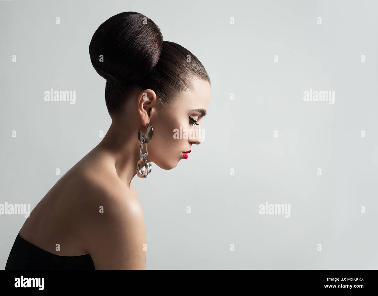 Pretty Young Woman With Hair Bun Hairstyle And Eyeliner Make Up
