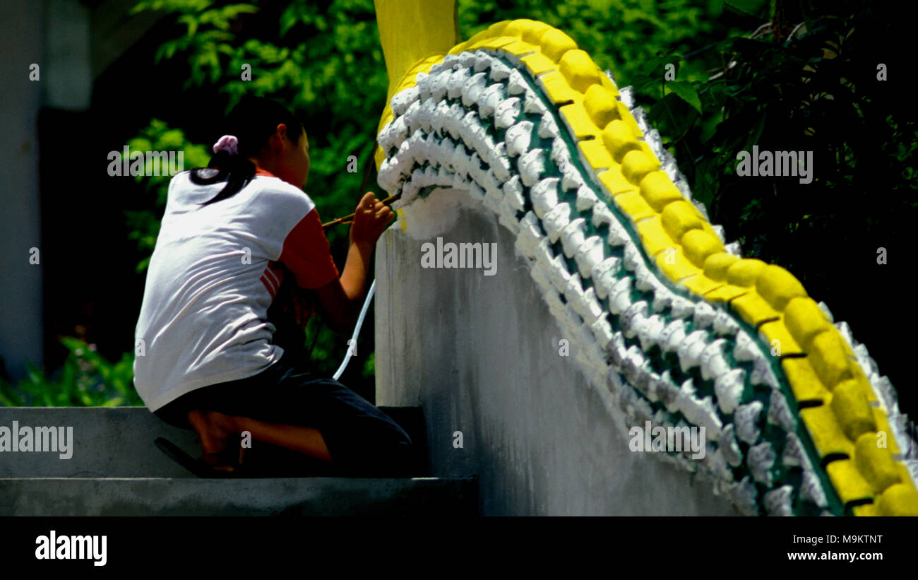 An indigenous Shan refugee woman from Myanmar (Burma) painting a dragon outside a Buddhist temple in northen Thailand. - Stock Image