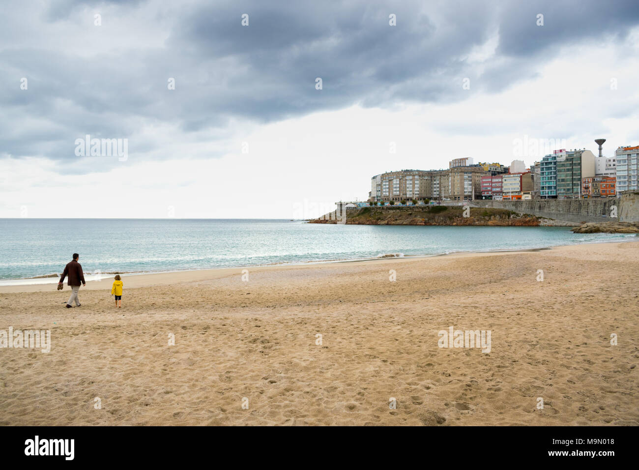 Father and daughter walking on a beach in Northern Spain under a cloudy sky - Stock Image