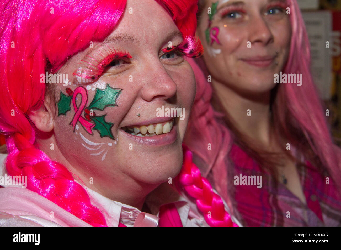 Woman in pink wig with holly painted on her face at a Christmas Fair - Stock Image