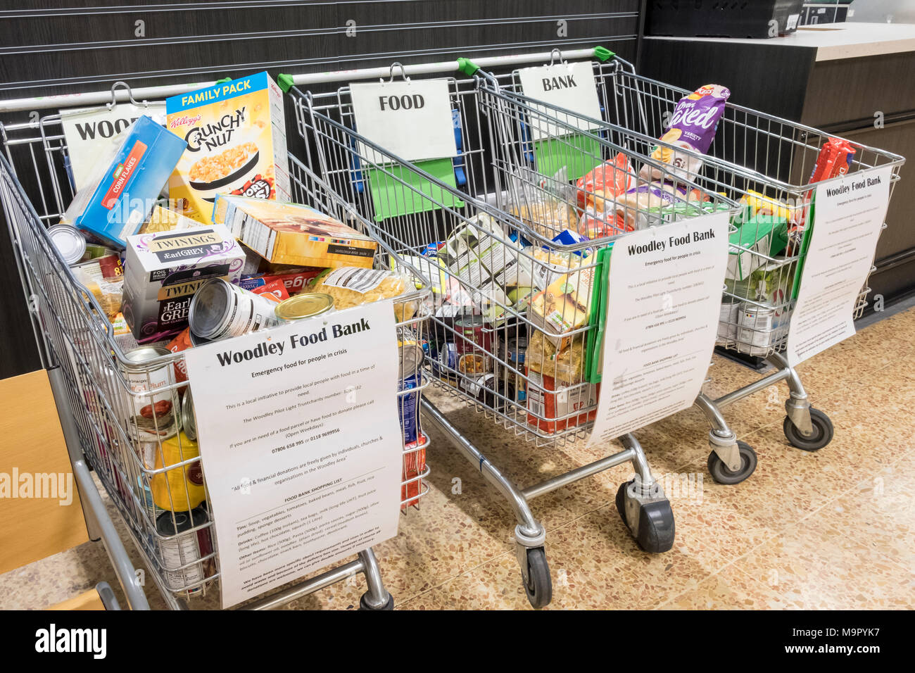 Food bank donations left in shopping trollies at an Asda supermarket. Reading, Berkshire, England, GB, UK Stock Photo