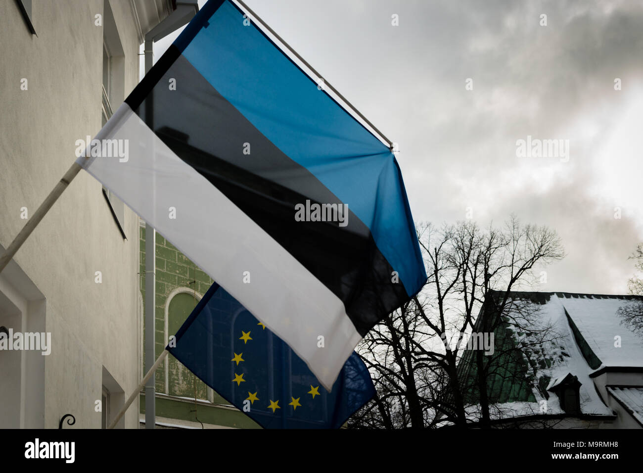 Estonian flag, flag of Estonia, waiving in the city. - Stock Image