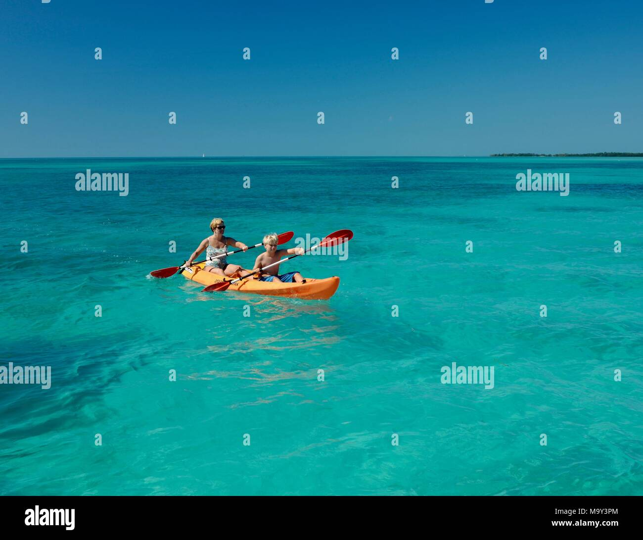 Mother and son kayaking in pristine, warm ocean water off Key West, Florida, USA - Stock Image